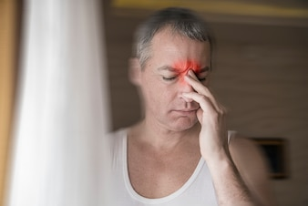 Mature attractive man looking worried, depressed, thoughtful and lonely suffering depression in work or personal problems Feeling hopeless. Depressed man keeping eyes closed and touching his face while standing near the window
