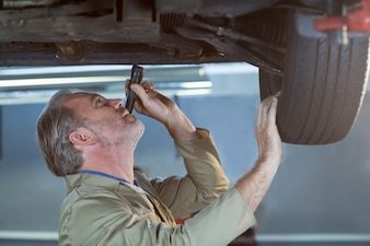 Mechanic examining car using flashlight