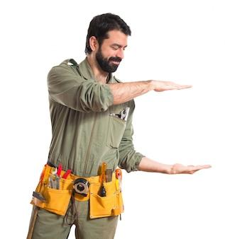 Mechanic holding something over white background