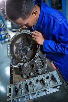 Mechanic repairing engine part