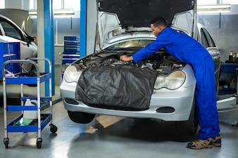 Mechanic servicing car engine