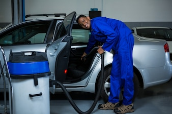 Mechanic servicing car with vacuum cleaner
