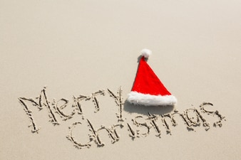 Merry Christmas written on sand with santa hat