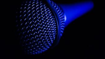 青い光と暗い背景でのマイクロフォン