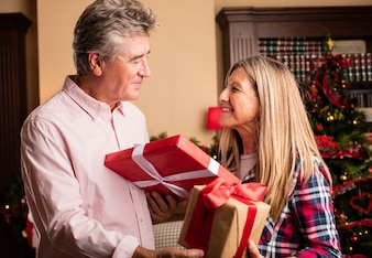 Middle aged woman giving a present to a man