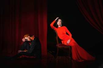 Military man and lady in red dress pose on the scene