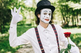 Mime with red rose in a park