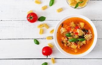 Minestrone, italian vegetable soup with pasta on wooden table