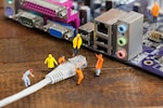 Miniature engineer and worker plug-in lan cable to computer