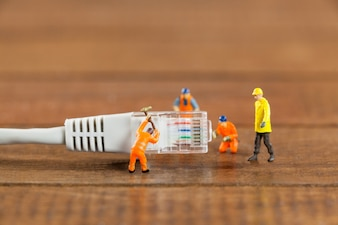 Miniature engineer and workers working with lan cable