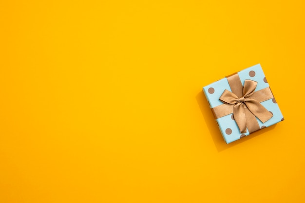 Minimalistic wrapped gift on yellow background