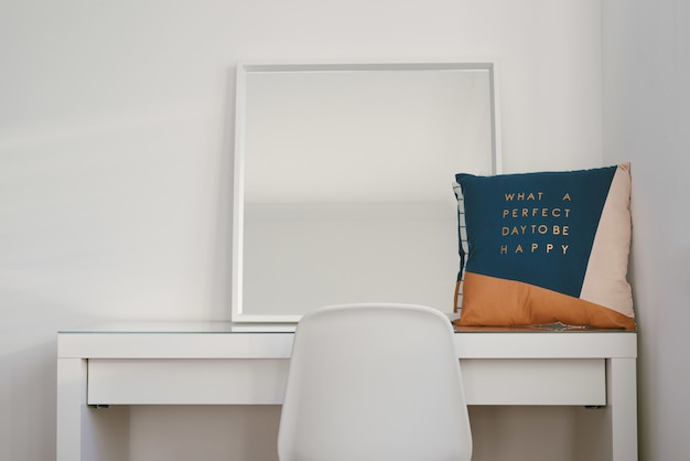Mirror and a cushion on a white table with a chair in front
