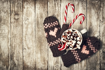 Mittens with hearts and a cup of coffee with chocolate and marshmallows