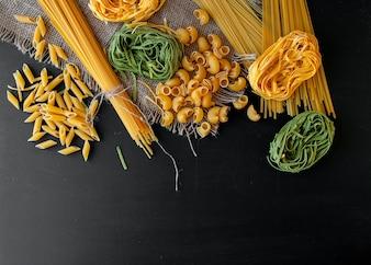 Mixed raw pasta on black background