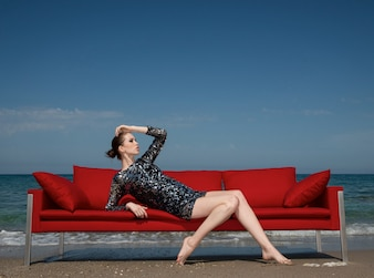 Model posing over a red couch
