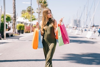 Model with shopping bags pointing something