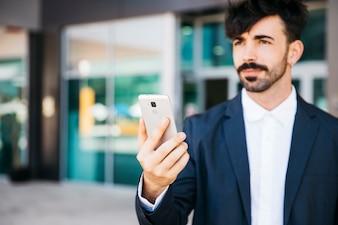 Modern businessman looking at smartphone