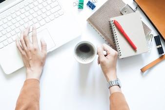 ラップトップを使用してコーヒーを飲む実業家と現代的な白オフィスの机のテーブル