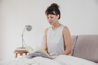 Modern woman reading in the bed