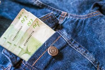ポケットのお金。ジーンズポケットに100ユーロ紙幣のクローズアップ。