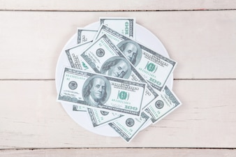 Money on white plate on wood table with space.