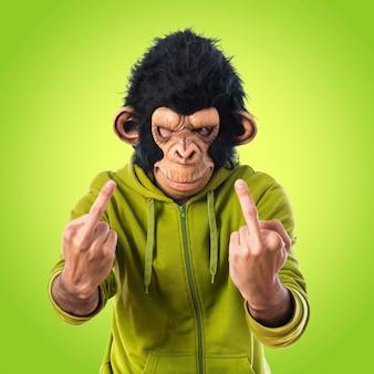 カラフルな背景にホーンのジェスチャーを作る猿の男