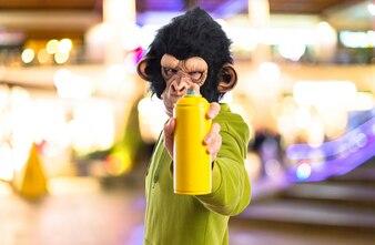 ぼんやりとした背景にスプレーを持つ猿の男