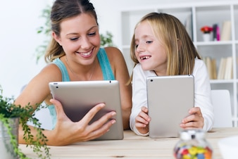 Mother and daughter looking at tablets