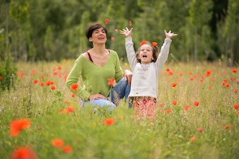 Mother and daughter playing in the meadow in spring