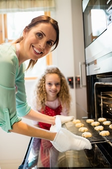 Mother and daughter preparing cookies in kitchen
