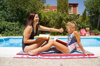 Mother and daughter sitting by pool smiling