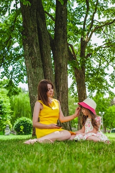 Mother and daughter sitting in a park with a tree background