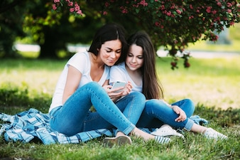 母と娘が公園に座ってリラックス