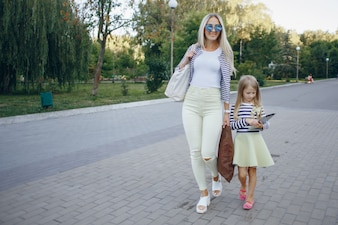 Mother and daughter walking while the girl looks at a tablet