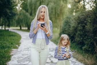 Mother and daughter walking with tablet and smartphone