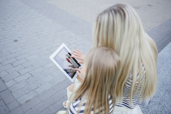 Mother and daughter with a tablet in hands
