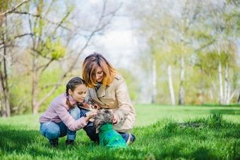 Mother and daughter with dog in the park