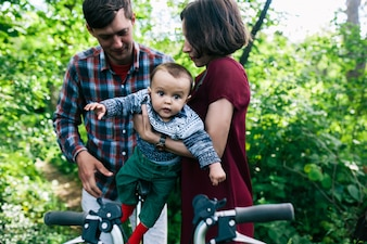 Mother and father putting child on bicycle