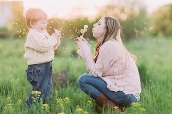 Mother and son blowing dandelions