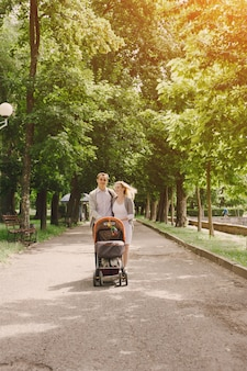 Mother and young father walking their baby in the park