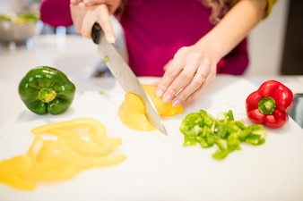 Mother assisting daughter in cutting vegetables in kitchen