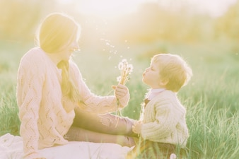 Mother blowing a dandelion