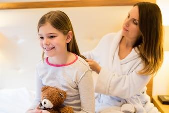 Mother combing her daughters hair in bedroom