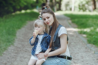 Mother crouching holding a hand to her daughter while eating an ice cream