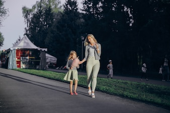 Mother eating an ice cream and her daughter pink cloud while walking