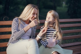 Mother giving her ice cream to her daughter