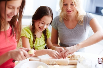 Mother helping her daughter with pizza dough