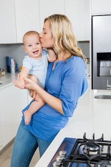 Mother holding her baby boy in kitchen