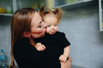 Mother kissing her daughter and girl with tongue out