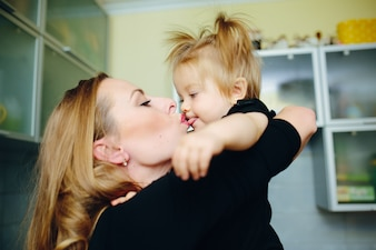 Mother kissing her daughter in the mouth